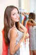 Beautiful girl with dresses near mirror