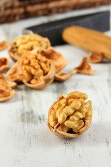 Broken walnuts with hammer on wooden table close-up