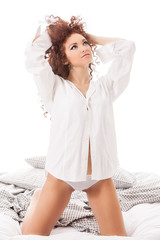 Attractive brunette with curly hairs wearing lingerie in the bed