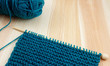 Garter stitch on knitting needle with teal yarn