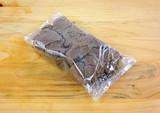 Plastic wrapped dark brown sugar on a wood cutting board