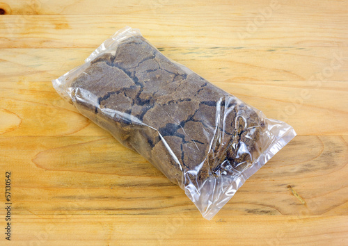 Plastic wrapped dark brown sugar on a wood cutting board