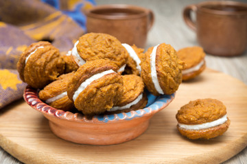 bowl of pumpkin cookies with cream filling on a wooden board