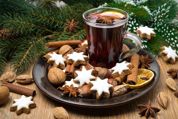 cookies in the shape of stars, spices and mulled wine on a plate