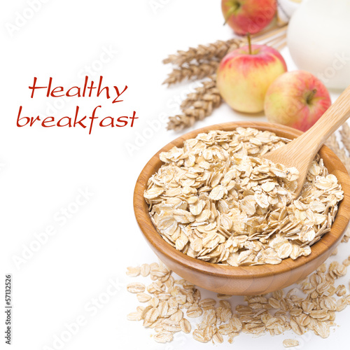 Oat flakes in a bowl and apples in the background, isolated
