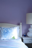 Detail of bed in bedroom with purpe wall