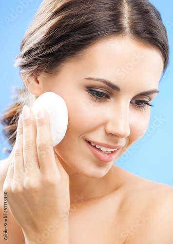 Young woman cleaning skin by cotton pad, over blue