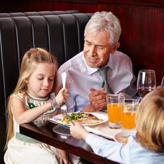 Opa redet mit Enkelin beim Essen