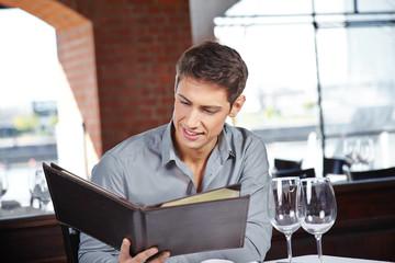 Mann im Restaurant schaut in Getränkekarte