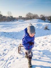 Small boy pulling a sledge