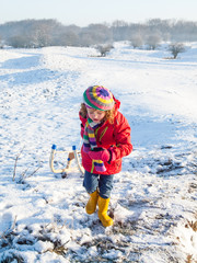 Small girl pulling a sledge in a snow covered dune landscape