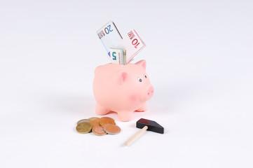 rosa Sparschwein mit Hammer Euro Scheinen und Euro Münzen