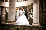 Beautiful married couple kissing in alcove with columns