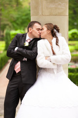 Newly married couple kissing under column
