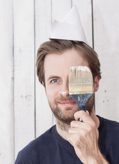Smiling man with a paint brush, renovation, painting walls.