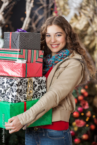 Woman Carrying Stacked Gift Boxes In Christmas Store