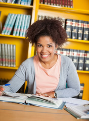 Female Student With Books Sitting At Table In Library