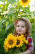 Little girl in a summer hat among sunflowers