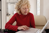 senior using a laptop on vacation, frowning