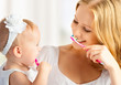 mother and daughter baby girl brushing their teeth together - 57146344