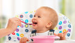 happy mother feeds funny  baby from  spoon - 57146349