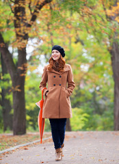Redhead girl with umbrella at autumn outdoor