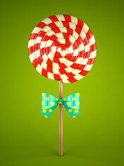 Lollipop with bow on green background