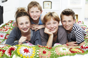 Four siblings lying on a bed