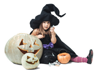 witch sits near the pumpkins and eating candy