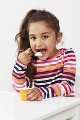 Young girl eating yoghurt in studio