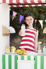 Young girl holding fruit juice bottle n fruit stall