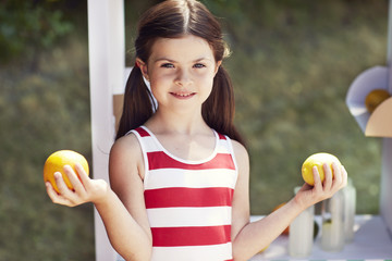 Young girl in striped dress holding fruit