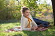 woman lying on bedding on green grass with ipad