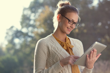 happy woman in glasses using tablet pc in the park