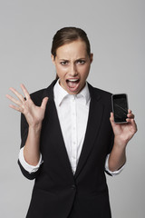 Portrait of shocked young businesswoman holding broken cellphone