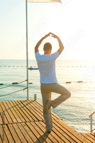 man standing on a pier on one leg and holds the balance