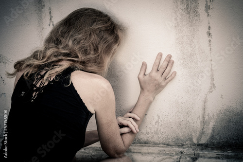 one sad woman sitting on the floor near a wall
