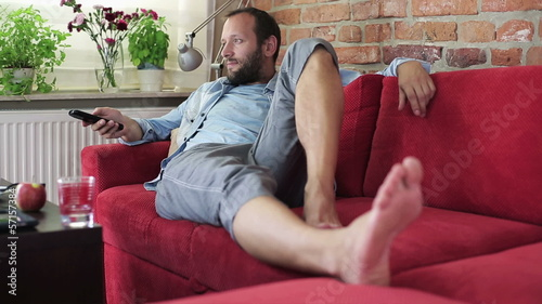 Man watching tv and drinking coffee
