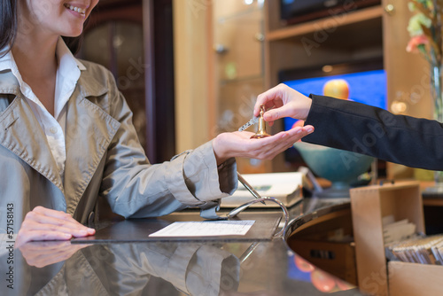 receptionist handing over keys to hotel room