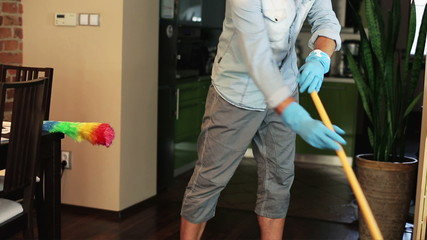 Man sweeping the floor at home