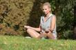 Mädchen sitzt entspannt auf der Wiese