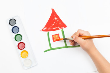 child draws house with watercolors