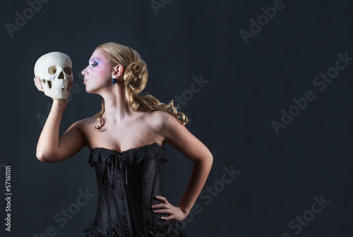 Girl with a skull on black background, studio shot