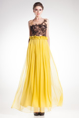 beautiful woman posing in long yellow dress with black lace