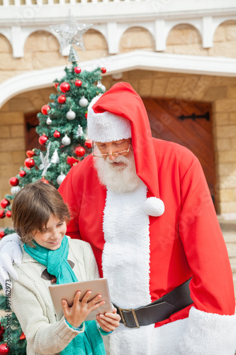 Santa Claus And Boy Using Digital Tablet
