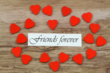 Friends forever card with little wooden hearts on wooden surface
