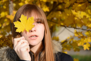 Young red-haired girl closed her eyes one sheet of yellow wedge