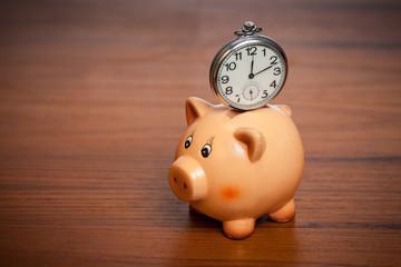 Pocket watch on a piggy bank