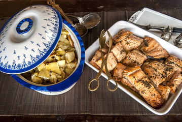 Rustic table with dishes of grilled salmon and sauteed potatoes