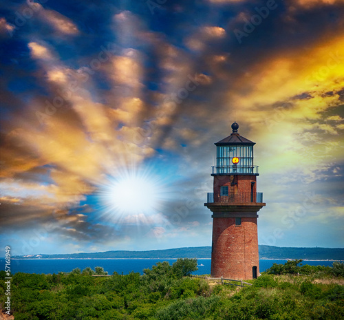 Lighthouse on a beautiful island. Sunset view with trees and sea